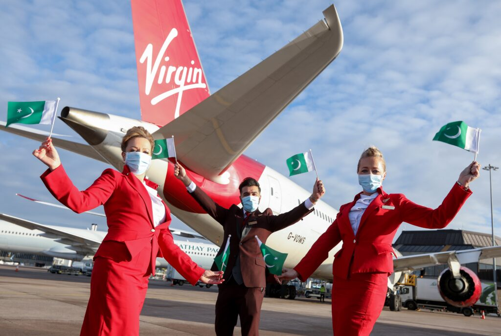 Virgin Atlantic staff wave Pakistani flag at Manchester Airport during their first flight to Pakistan
